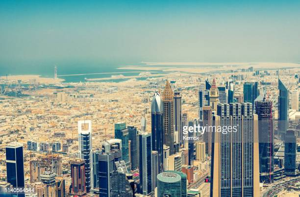 dubai skyscrapers skyline from above with a view of the desert and the persian gulf - east stock pictures, royalty-free photos & images