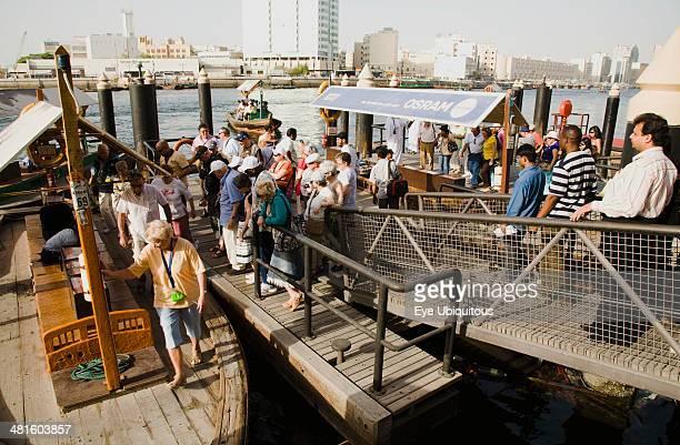 UAE Dubai Tourists board Abra water taxi moored on the Creek with Bur Dubai heritage skyline behind