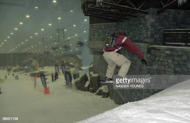 A snowboarder shows his skills as skiing officially started 02 December 2005 at Dubai's new indoor ski resort a manmade mountain scene as big as...