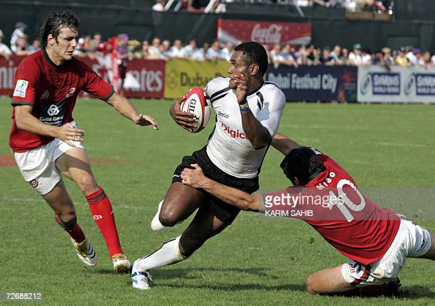 Dubai, UNITED ARAB EMIRATES: Fiji player Ameniassi Nava Kuruinovo tries to escape from Tiago Girao and Antonio de Aguilar of Portugal , during their...