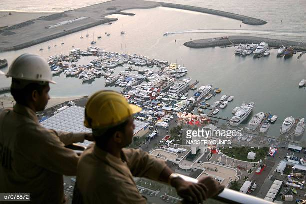 Dubai, UNITED ARAB EMIRATES: Indian workers watch the openning of Dubai's international boat show from the 50th floor of the tower which is beign...