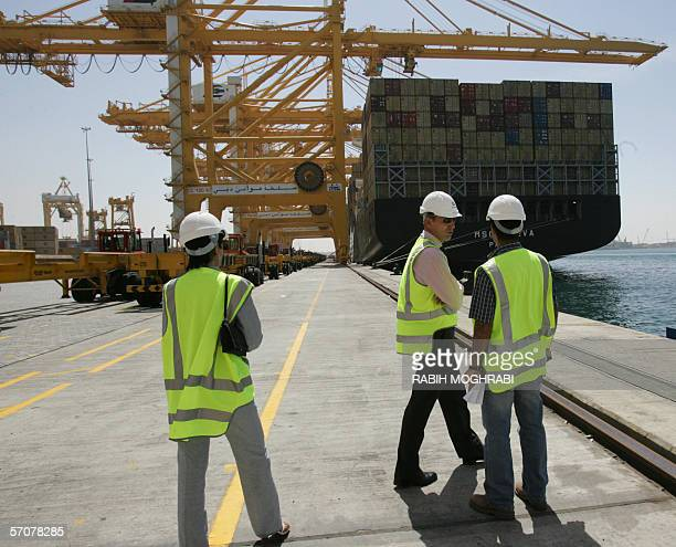 Official workers stand by as cranes unload containers in the Dubai port of Jebel Ali 14 March 2006 Dubai Ports World owned by the United Arab...