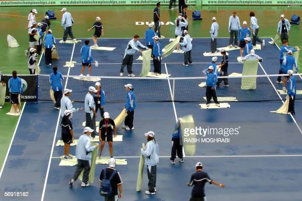 Dubai, UNITED ARAB EMIRATES: Staff of the Dubai Open tournament dry the central tennis court after heavy rain in the oil-rich Gulf emirate, 23...