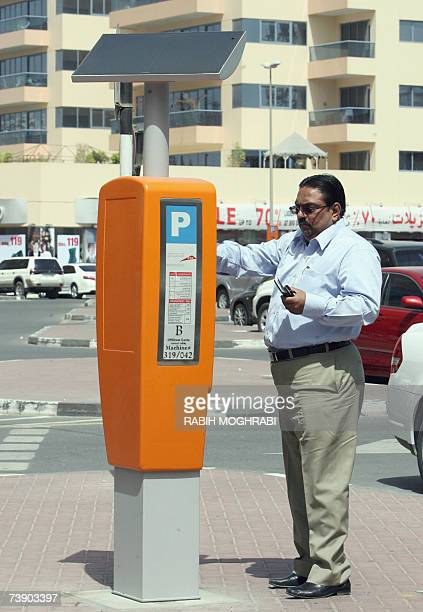 TO GO WITH AFP FEATURE STORY IN ENGLISH BY ALI KHALIL A Dubai resident puts buys a ticket at a parking meter powered by solar energy in Dubai 16...