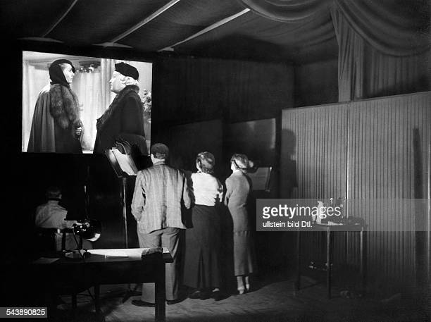 Dubbing artists in the studio standing in front of a movie screen Photographer Curt Ullmann Published by 'Hier Berlin' 29/1936Vintage property of...