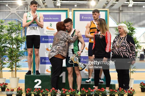Dublin , Ireland - 1 March 2020; Dean Adams of Ballymena and Antrim AC is presented with the Craig Lynch cup by Craig's mother Anne Lynch, second...