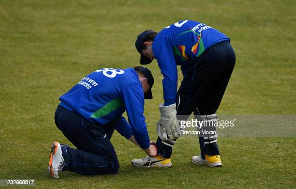 Dublin , Ireland - 1 May 2021; Shane Getkate of North West Warriors ties the shoelaces of team-mate and wicketkeeper Stephen Doheny during the...