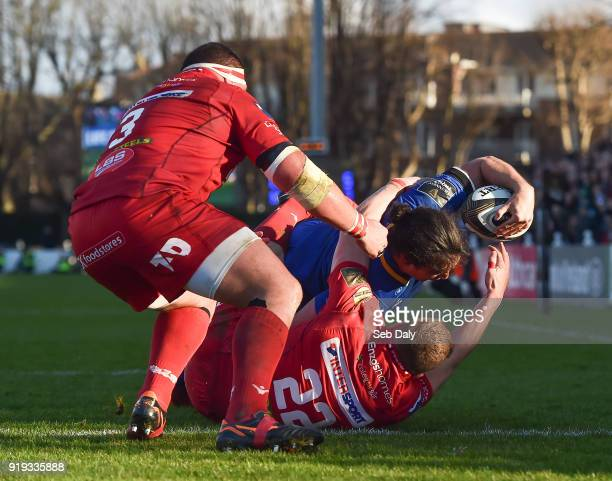 Dublin Ireland 17 February 2018 James Lowe of Leinster goes over to score his side's second try despite the tackle of Corey Baldwin of Scarlets...