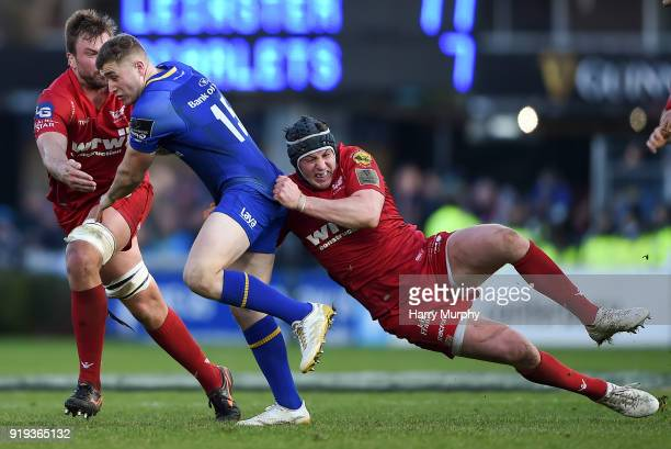 Dublin Ireland 17 February 2018 Jordan Larmour of Leinster is tackled by Ryan Elias right and David Bulbring of Scarlets during the Guinness PRO14...