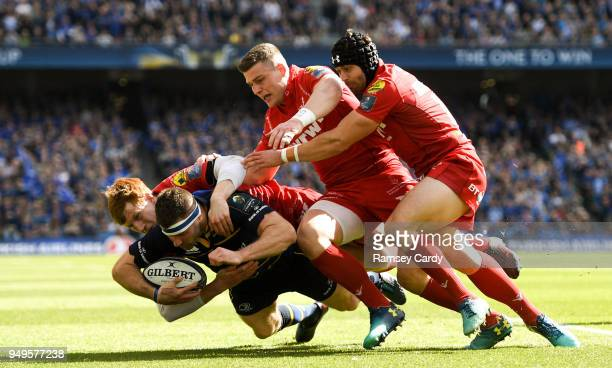 Dublin Ireland 21 April 2018 Fergus McFadden of Leinster is tackled by Rhys Patchell left Scott Williams centre and Leigh Halfpenny of Scarlets...
