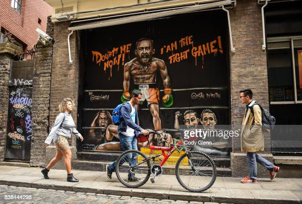 Dublin Ireland 24 August 2017 Pedestrians pass in front of a mural of Conor McGregor and Floyd Mayweather outside Sin Nightclub on Sycamore Street in...