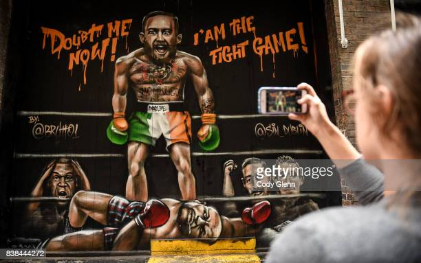 Dublin Ireland 24 August 2017 Whitney Baillie from Syracuse New York takes a photo of a mural of Conor McGregor and Floyd Mayweather outside Sin...