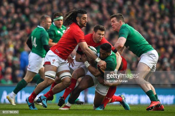 Dublin Ireland 24 February 2018 Bundee Aki of Ireland supported by teammate Chris Farrell is tackled by Josh Navidi and Dan Biggar of Wales during...