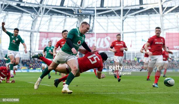 Dublin Ireland 24 February 2018 Keith Earls of Ireland pursues his kick forward alongside Leigh Halfpenny of Wales during the NatWest Six Nations...