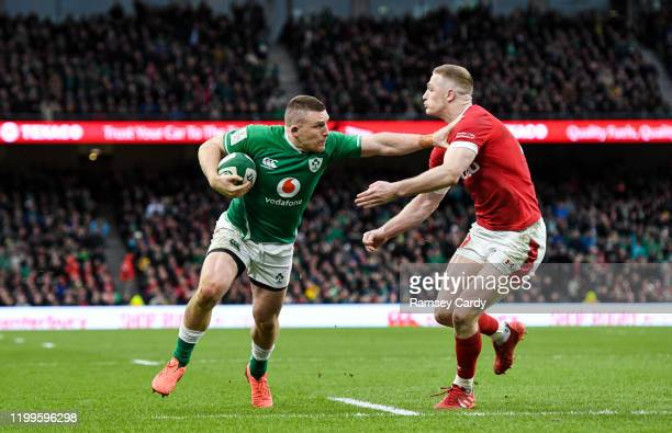 Dublin , Ireland - 8 February 2020; Andrew Conway of Ireland on his way to scoring his side's fourth try despite the tackle of Johnny McNicholl of...