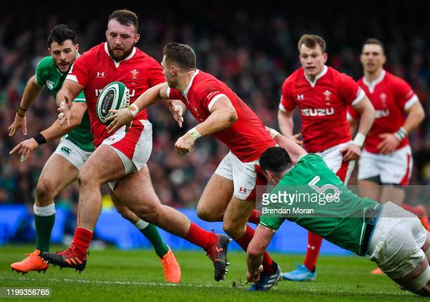 Dublin Ireland 8 February 2020 Dan Biggar of Wales offloads to Dillon Lewis of Wales as he his tackled by James Ryan of Ireland during the Guinness...