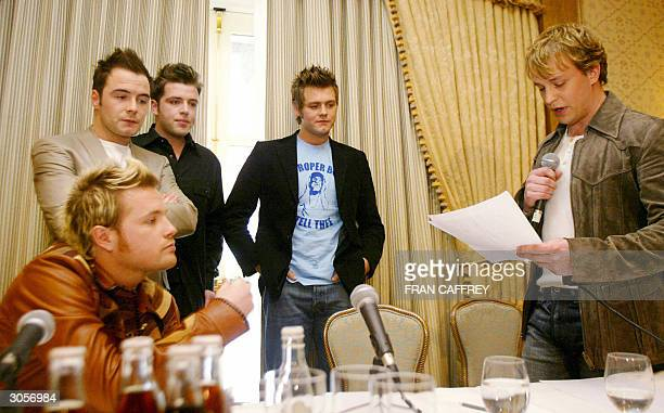 Westlife band members Nicky Byrne Shane Filan Mark Feehily Bryan McFadden listen while Kian Egan reads a statement at press conference to announce...