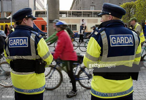Dublin police officers keep an eye on bicycle riders during a demonstration leading up to May Day in Dublin 30 April 2004 Irish police are laying on...