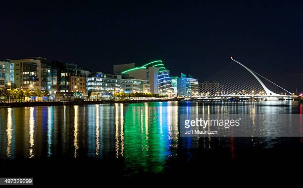 Dublin's illuminated buildings reflect on the River Liffey at night.