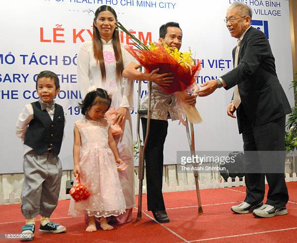Duc Nguyen receives a flower bunch to celebrate 25th anniversary of the surgically separated with his conjoined brother Viet at a hospital on October...