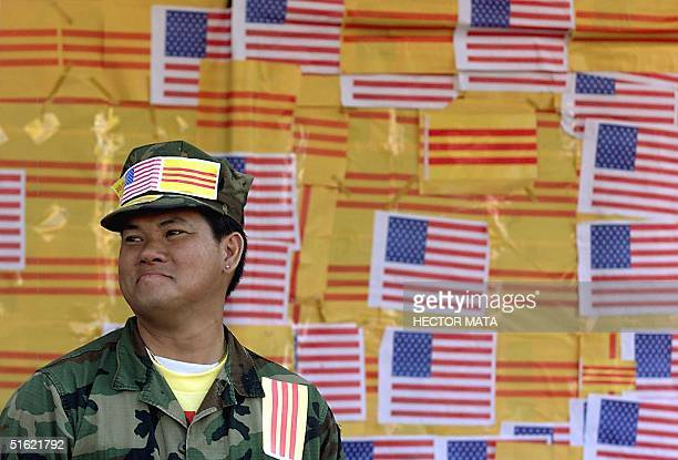 Duc Tan Nguyen a Vietnamese immigrant stands near the entrance of a video shop covered with US and Vietnam flags 27 February in Little Saigon...