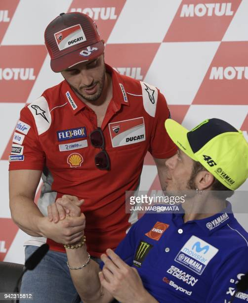 Ducati biker Andrea Dovizioso of Italy and Yamaha biker Valentino Rossi of Italy shake hands during a press conference in the framework of the...