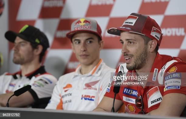 Ducati biker Andrea Dovizioso of Italy talks to the press next to Honda biker Marc Marquez of Spain and Honda biker Cal Crutchlow of Britain during a...