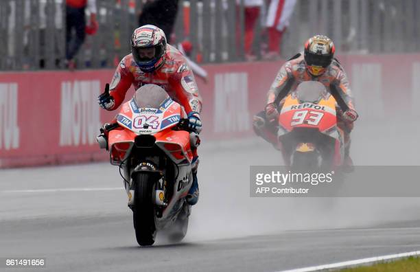 Ducati rider Andrea Dovizioso of Italy flashes thumbup while receiving a checkered flag ahead of Honda rider Marc Marquez of Spain during the MotoGP...