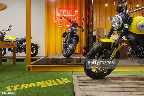 A Ducati Scrambler Icon motorcycle right and a Ducati Scrambler Urban Enduro motorcycle center manufactured by Ducati Motor Holding SpA stand on...