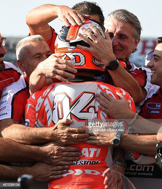 Ducati Team rider Andrea Dovizioso of Italy is celebrated by team members at the parc ferme after getting the pole position in the MotoGPclass...