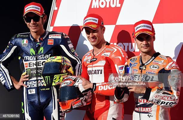 Ducati Team rider Andrea Dovizioso of Italy smiles with Movistar Yamaha MotoGP rider Valentino Rossi of Italy and Repsol Honda Team rider Dani...