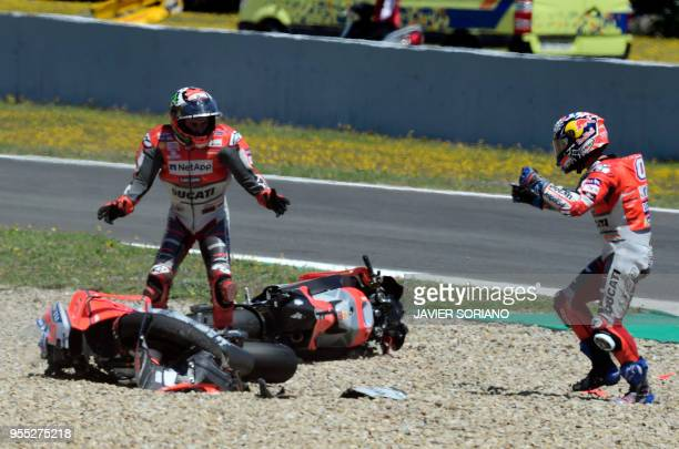 TOPSHOT Ducati Team's Italian rider Andrea Dovizioso and Ducati Team's Spanish rider Jorge Lorenzo stand next to their bikes after falling down...