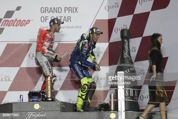 Ducati Team's Italian rider Andrea Dovizioso and Movistar Yamaha MotoGP's Italian rider Valentino Rossi celebrate on the podium after winning the...