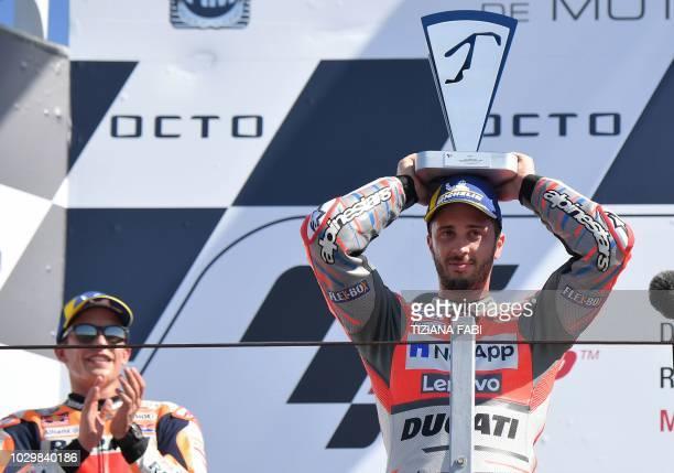 Ducati Team's Italian rider Andrea Dovizioso celebrates next to second placed Repsol Honda Team's Spanish rider Marc Marquez on podium after winning...