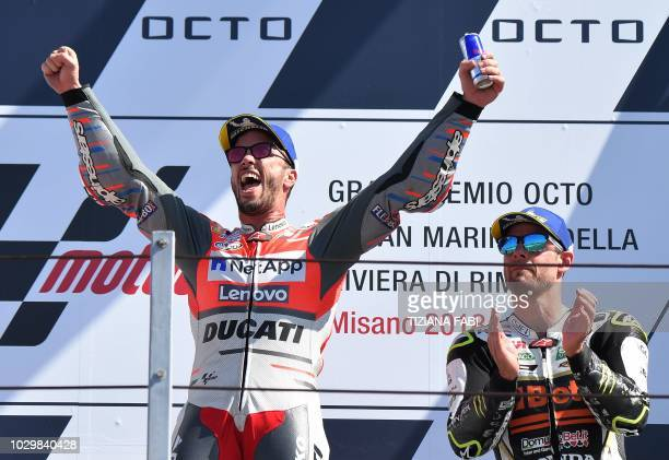 TOPSHOT Ducati Team's Italian rider Andrea Dovizioso celebrates victory as third placed LCR Honda Castrol's British rider Cal Crutchlow applauds on...