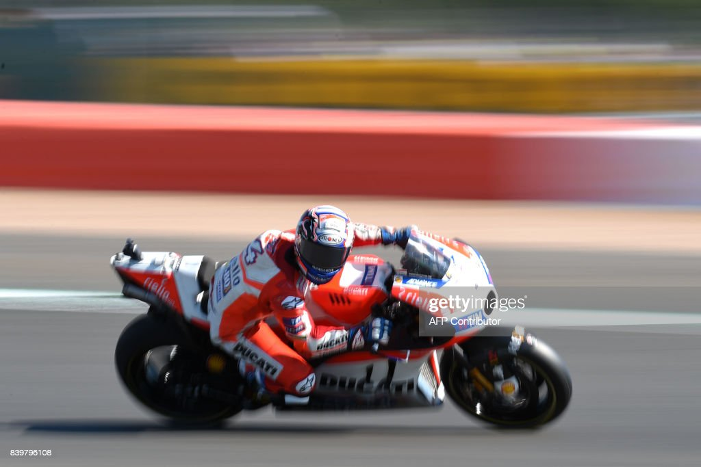 TOPSHOT - Ducati Team's Italian rider Andrea Dovizioso exits Village Corner during the MotoGP Warm Up session of the British Grand Prix at Silverstone circuit in Northamptonshire, southern England, on August 27, 2017. /