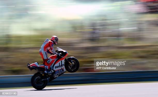 Ducati Team's Italian rider Andrea Dovizioso makes a wheelie during the qualification of the Moto GP Grand Prix of the Czech Republic in Brno on...