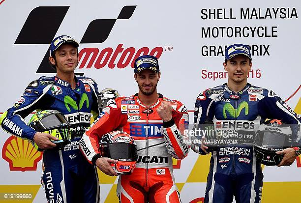 Ducati Team's Italian rider Andrea Dovizioso poses on the podium after winning the 2016 Malaysian MotoGP at the Sepang International circuit on...