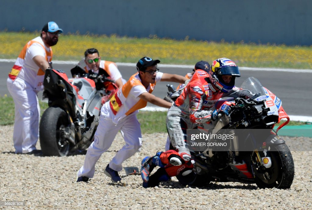 Ducati Team's Italian rider Andrea Dovizioso pushes his bike after falling down during the MotoGP race of the Spanish Grand Prix at the Jerez Angel Nieto racetrack in Jerez de la Frontera on May 6, 2018.