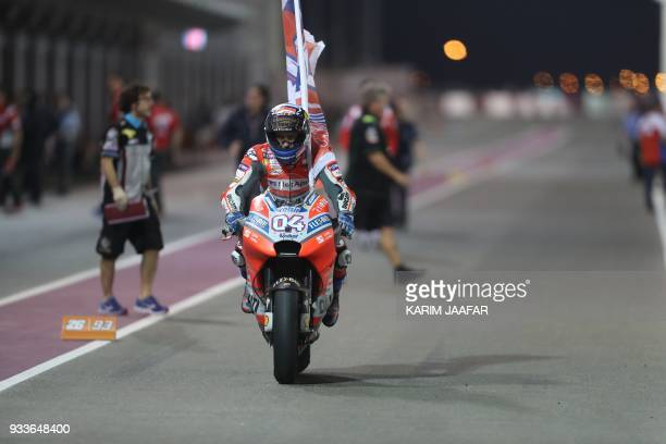 Ducati Team's Italian rider Andrea Dovizioso rides his Ducati and holds a flag after winning the 2018 Qatar Moto GP Grand Prix at the Losail...