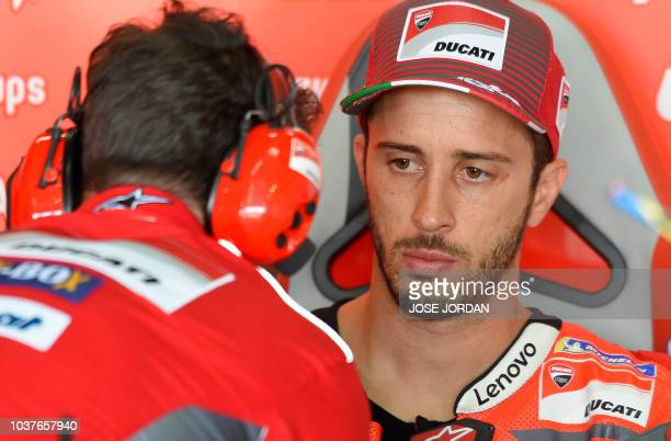 Ducati Team's Italian rider Andrea Dovizioso speaks with mechanics during the MotoGP fourth free practice of the Aragon Grand Prix at the Motorland...