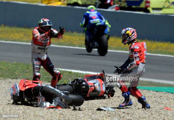 TOPSHOT Ducati Team's Italian rider Andrea Dovizioso talks with Ducati Team's Spanish rider Jorge Lorenzo after falling down during the MotoGP race...