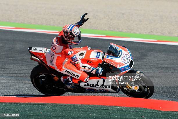 Ducati Team's Italian rider Andrea Dovizioso waves to fans from his bike during the third MotoGP free practice session of the Moto Grand Prix de...