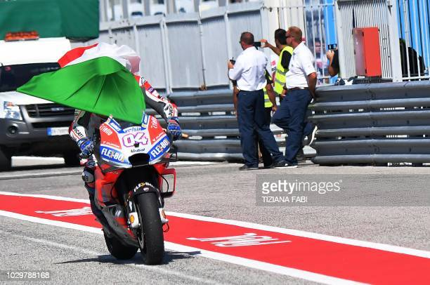 TOPSHOT Ducati Team's rider Italian Andrea Dovizioso has an Italian flag covering his helmet as he arrives in the pits after he celebrate winning the...