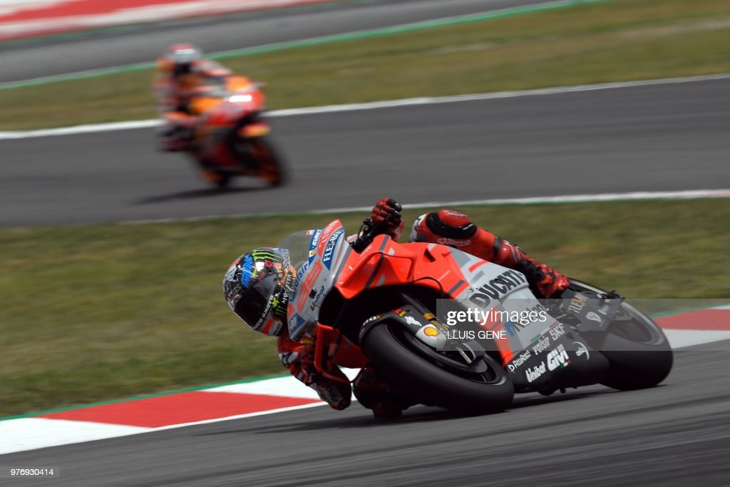 TOPSHOT - (FromL) Ducati Team's Spanish rider Jorge Lorenzo and Repsol Honda Team's Spanish rider Marc Marquez ride during the Catalunya MotoGP Grand Prix race at the Catalunya racetrack in Montmelo, near Barcelona on June 17, 2018.