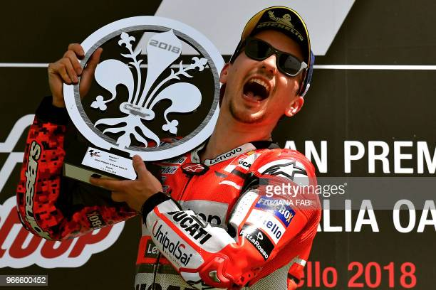 Ducati Team's Spanish rider Jorge Lorenzo celebrates on the podium after he won the Moto GP Grand Prix at the Mugello race track on June 3 2018