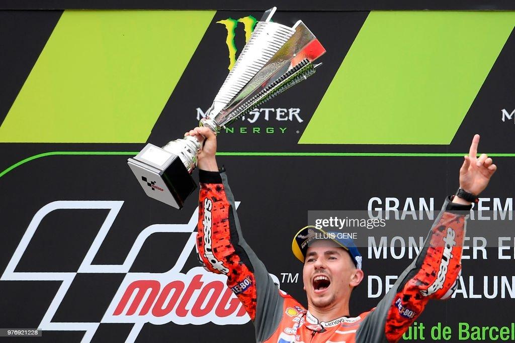 TOPSHOT - Ducati Team's Spanish rider Jorge Lorenzo celebrates on the podium after winning the Catalunya MotoGP Grand Prix race at the Catalunya racetrack in Montmelo, near Barcelona on June 17, 2018.