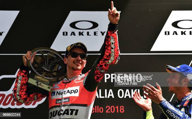 Ducati Team's Spanish rider Jorge Lorenzo celebrates on the podium next to third placed Movistar Yamaha's Italian rider Valentino Rossi after he won...