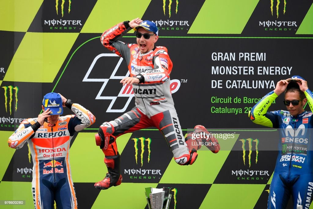 TOPSHOT - Ducati Team's Spanish rider Jorge Lorenzo (C) celebrates on the podium NEXT TO Repsol Honda Team's Spanish rider Marc Marquez (L), second placed, and Movistar Yamaha MotoGP's Italian rider Valentino Rossi (R), third place, after winning the Catalunya MotoGP Grand Prix race at the Catalunya racetrack in Montmelo, near Barcelona on June 17, 2018.