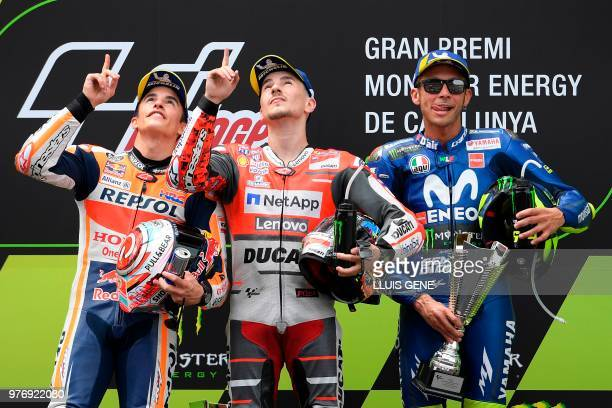 TOPSHOT Ducati Team's Spanish rider Jorge Lorenzo first placed and Repsol Honda Team's Spanish rider Marc Marquez second placed look up in memory of...